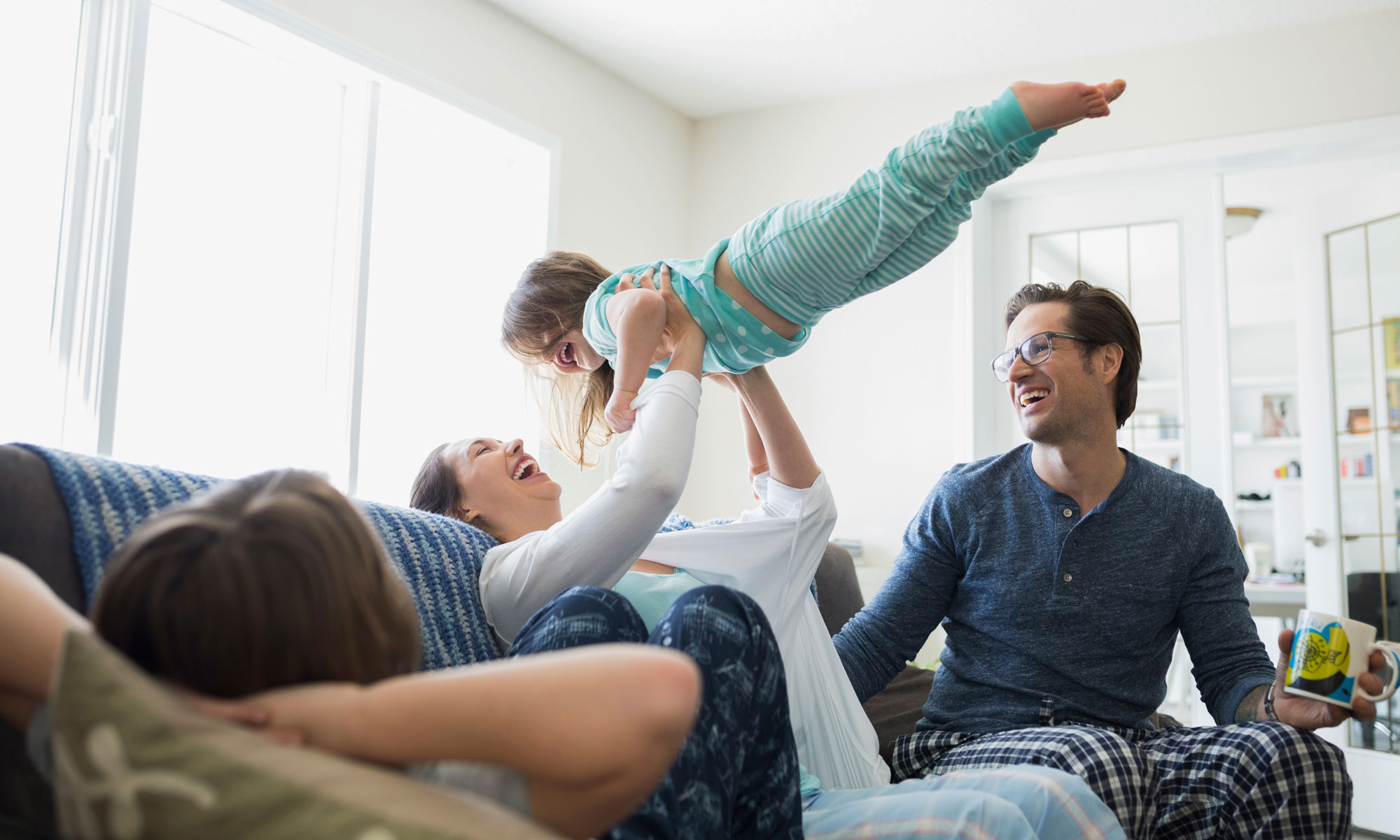 Family dressed in pajamas holding child in the air.